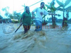 TERGANGGU : Aktivitas jalan desa setempat lumpuh. Lantaran terendam air dengan arus yang kuat