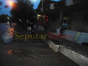 BERTAHAN : Warga enggan mengungsi meski banjir sudah merendam rumah mereka