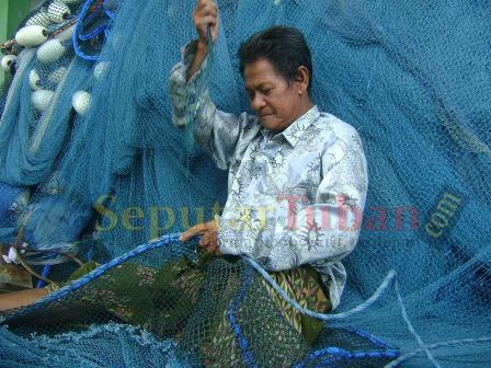 PENDAPATAN BERKURANG : Karena angin kencang, nelayan tidak melaut dan memanfaatkan waktu luangnya untuk memperabaiki jaring