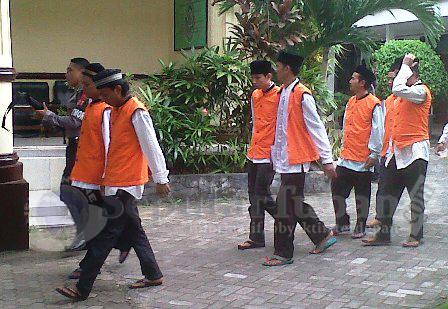 MENGELAK : Para terdakwa saat memasuki PN Tuban untuk menjalani persidangan