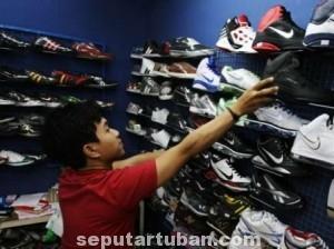 OBRAL BESAR: Seorang remaja tengah memilih sepatu dengan diskon gede-gedean.