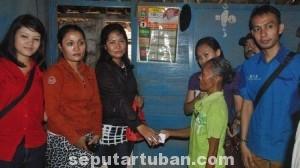 SAMA RATA: Sarini terharu bercampur kaget saat karyawan Oke Pub dan Karaoke memberikan bantuan di rumahnya Desa Hargoretno, Kecamatan Kerek, Kamis (19.06/2014) siang.