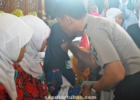 BERBAGI KEBAHAGIAAN : Kapolres Tuban, AKBP Ucu Kuspriyadi mencium anak yatim saat memberikan santunan secara simbolis di Pendopo Pemkab Tuban. Sabtu (21/6/2014)