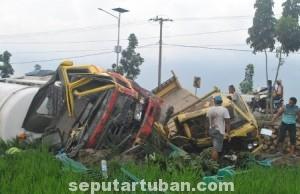 PARAH : Kondisi kedua truk usai tabrakan hingga terguling ke sawah