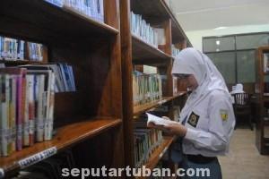 LENGANG: Seorang siswa perempuan tengah mencari buku di salah satu sudut etalase Perpustakaan Umum Tuban, Rabu (16/07/2014).