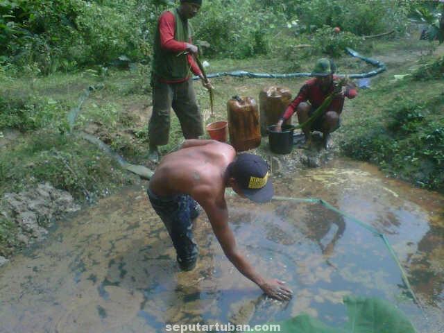 MEMISAH AIR : Warga saat mengambil air bercampur minyak untuk dijual