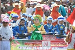 HARMONISASI: Wajah anak-anak yang lugu dan imut-imut tampak begitu begitu ceria dalam Kirab Drum Band, Rabu (13/08/2014) sore.