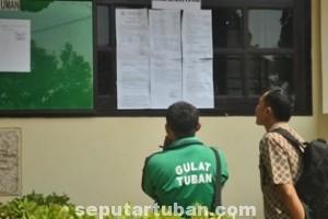 SERIUS: Dua orang pelamar CPNS rekrutmen tahun 2014 mencermati lembaran kertas berisi jumlah formasi dan latar pendidikan yang dibutuhkan di kantor BKT Tuban, Jumat (05/09/2014) siang.