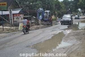 SERAMPANGAN: Gara-gara kecantol mesin eksavator saluran pipa PDAM di Jalan Raya Desa Sambonggede, Merakurak, Rabu (03/09/2014) pagi, jebol.