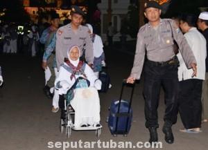 TAMU ALLAH : Dua anggota Sat Sabhara Polres Tuban membantu CJH memasuki komplek Pendopo Krido Manunggal Pemkab Tuban, Selasa (23/09/2014)