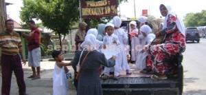 POLOS: Anak-anak siswa RA dengan ceria naik kendaraan bak terbuka saat akan mengikuti acara manasik haji yang digelar Kantor Kemenag Tuban, Senin (13/10/2014) pagi. (foto: MUHLISHIN)