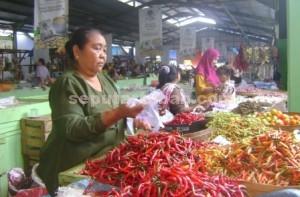 MENUNGGU PEMBELI: Setiyani, seorang pedagang sayur di Pasar Baru Tuban, Jumat (07/11/2014) pagi. foto:ARIF AHMAD AKBAR