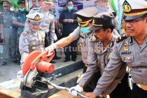 TIDAK STANDAR: Kapolres Tuban AKBP Ucu Kuspriyadi memotong knalpot blong menandai prosesi pemusnahan yang digelar Selasa (30/12/2014) siang.
