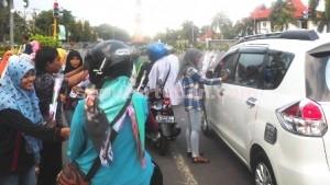 UNTUK IBU: Para pelajar yang mengatasnakam dirinya Psupres Kabupaten Tuban membagi untaian bunga mawar kepada warga yang melintas di Jalan Sunan Bonang, Senin (22/12/2014) siang.