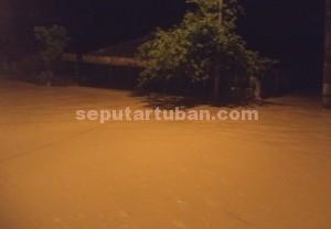 TENGGELAM : Rumah milik Sutamat (33), yang berada dinggir jalan poros kecamatan terendam separuh lebih, Sabtu (27/12/2014) malam
