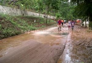 GERAK CEPAT : Petugas BPBD sedang membersihkan jalan yang dipenuhi lumpur