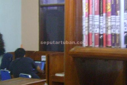 KASMARAN : Pasangan remaja ini nampak bermesraan disalah satu sudur ruangan Perpustakaan Umum Pemkab Tuban, Kamis (11/12/2014) siang.