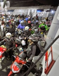 MENGULAR: Hari pertama pemberlakuan harga baru premium dari Rp 7.600 menjadi Rp 6.600 per liter, membuat warga ramai-ramai mendatangi SPBU untuk mengantre premium. Antrean didominasi sepeda motor yang sebagian besar mengisi penuh tangkinya.