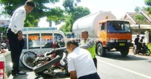KECELAKAAN: Petugas Kanit Laka Lantas Polres Tuban mengevakuasi sepeda motor korban di Jalan Raya KM 5 Widengan, Kamis (29/01/2015) pagi.