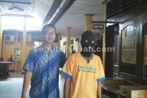 DILUAR BATAS : Tersangka pencabulan didepan anaknya saat di Mapolres Tuban, Jumat (16/01/2014)