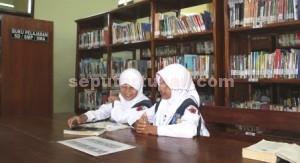 ------- MEMBACA: Dua remaja SMP menghabiskan waktunya di Perpustakaan Umum Tuban saat pulang awal dari sekolah, Senin (23/03/2015) siang. foto: WANTI TRI APRILIANA