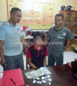 KOMPAK: Serda Koirul Mukid (kiri) dan Bripka Wahyu Indra (kanan) bersama terduga pelaku serta barang bukti karnopen serta uang tunai di Mapolsek Tuban, Rabu (01/04/2015) siang.