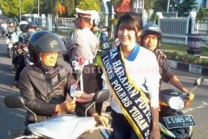 Semangat : Salah satu Duta Lalu Lintas Polres Tuban saat membagikan bunga kepada pengguna jalan
