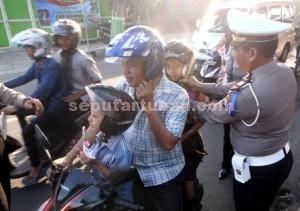 Dikmas Lantas : Kasat Lantas Polres Tuban, AKP Muchamad Faqih saat memberikan helm SNI kepada pengendara sepeda motor