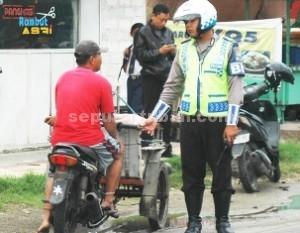SIMPATIK: Seorang anggota Satlantas Polres Tuban memberikan pengarahan kepada seorang warga yang menggunakan bentor atau becak motor, Kamis (02/04/2015) siang. foto: ARIF AHMAD AKBAR