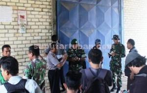 BARANG BUKTI: Aparat Koramil Montong dan Polsek setempat ketika berada di mulut gudang yang diduga menimbun pupuk bersubsidi.