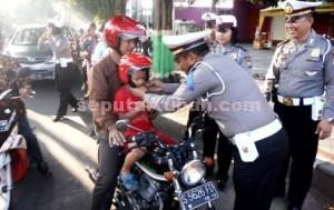 LAUNCHING: Jajaran Satlantas Polres Tuban memberikan helm untuk anak dalam acara sosialisasi stop N go di Jalan Basuki Rahmat, Senin (25/05/2015) pagi.