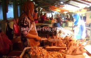 TIDAK KAGET: Kartini, seorang penjual daging ayam di Pasar Baru Tuban, Senin (01/06/2015) pagi.