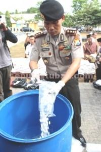 PIL SETAN: Kapolres Tuban AKBP Arif Guruh Darmawan melarutkan pil karnopen dalam acara pemusnahan barang bukti, Jumat (26/06/2015) pagi.