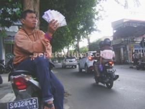 OPTIMIS: Salah seorang jasa penuakran uang recehan menunggui pembeli di Jalan Basuki Rahmad Tuban, Jumat (26/06/2015) pagi.