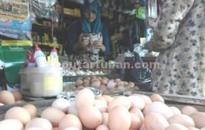 TELUR BURAS: Sriyatun tengah melakukan transaksi dengan pemebli di stan miliknya yang berada di Pasar Baru Tuban, Jumat (19/06/2015) pagi.