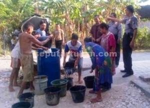 KEMANUSIAAN: Jajaran Polsek Semanding saat memberikan droping air bersih ke Desa Genaharjo.