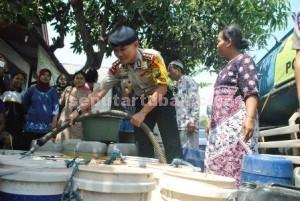 OPERASI KEKERINGAN: Kapolres Tuban, AKBP. Guruh Arif Darmawan, saat memberikan bantuan air bersih di Desa Sidoharjo, Kecamatan Senori, Jumat (18/09/2015).