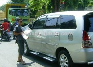 SEMANGAT : Ali Imron saat akan menjual koran kepada pengguna jalan