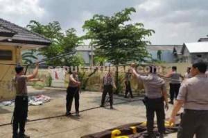 Kerjasama : Anggota Polres Tuban saat mendirikan tenda bersama-sama di halaman Gudang Logistik KPU Kab. Tuban untuk dipakai penjagaan.