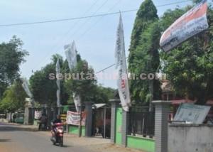 KONTRA DIKSI : Spanduk penolakan warga dipasang bersebelahan dengan umbul-umbul PT Semen Indonesia di salah satu kantor di Desa Gaji