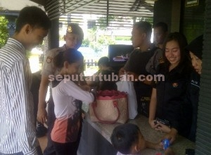 SIAGA PENUH : Barang bawaan tamu diperiksa personil Polres Tuban di pos penjagaan.