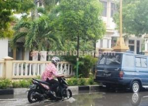 TERGENANG : Pemotor ekstra pelan saat melintasi genangan air di depan Kantor Dinsosnakertran