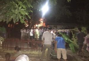 RESAH : Warga bahu membahu memadamkan api yang masih berkobar membakar rumah korban