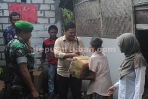 BERBAGI : pimpinan seputartuban.com, Cipnal Muchlip M, secara simbolis menyerahkan bantuan kepada Sriatun (74) wanita sebatangkara. Disaksikan Dandim 0811/Tuban dan Kepala Desa Kedungharjo (berjilbab)