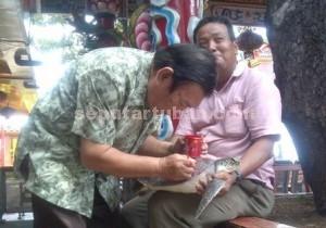 STOP MALAPETAKA : Seorang warga sedang menulis diatas punggung penyu yang akan dilepas di laut Tuban sebagai ritual buang bala