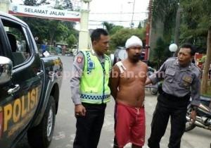 DIAMANKAN : Pelaku saat dibawa petugas. Saat diperiksa dia tetap tidak mengaku identitasnya