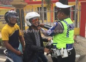 PEDULI : Anggota Polantas saat membenahi tali helm pemotor agar benar