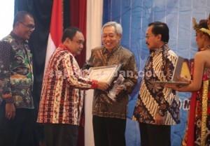 PRESTASI : Ketua Umum PWI Pusat, Margiono didampingi Ketua PWI Jatim, Akhmad Munir menyerahkan award kepada Direktur Utama PT Semen Indonesia, Suparni