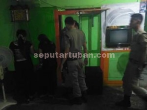 DITANGKAP : Petugas Sat Pol PP saat mengamankan 2 wanita di sebuah warung pangkalan truk Mamer