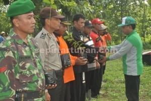 SIMBOLIS : Camat Montong, Agus Wijaya saat menyerahkan bibit pohon kepada perwakilan peserta apel